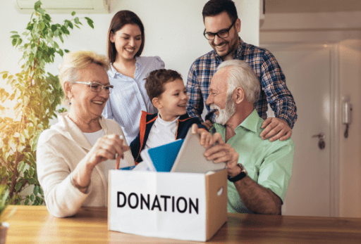 group of family sitting around a donation box